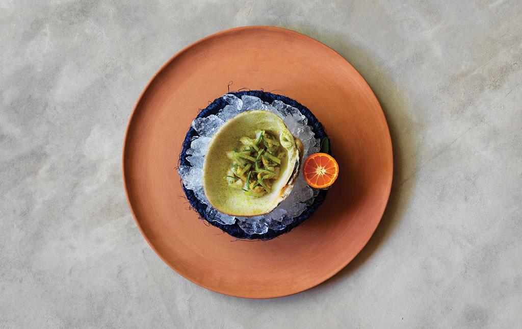 Almeja melón del mar de Cortés, servida con hierbas de la playa y mandarina